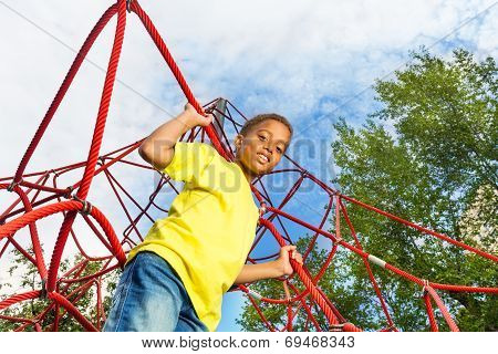 Funny boy holds and stands on red ropes