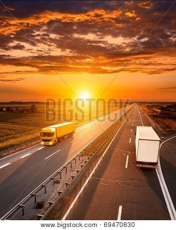 Two Trucks On The Highway At Sunset