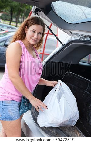 Happy Smiling Woman Putting Shopping Bags Into The Car Trunk