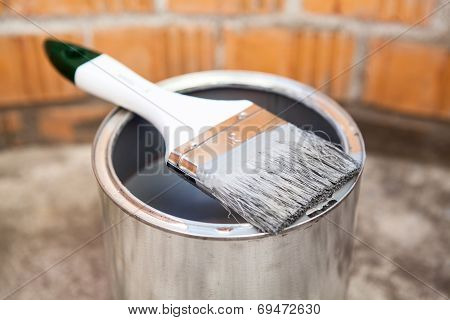 Paint Brush In Grey Color Laying On Can
