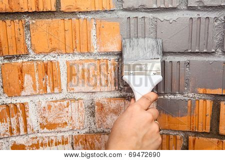 Human Hand With Grey Colored Brush Painting Brick Wall