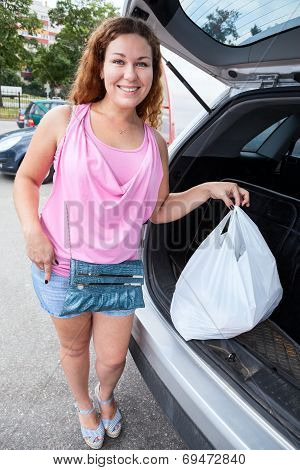 Fish-eye Image Of Shopper With Bag Loading In Car Trunk