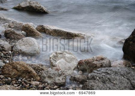 Waves Over Rocky Landscape