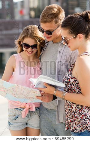 friendship, travel, tourism, vacation and people concept - smiling friends with map and city guide outdoors