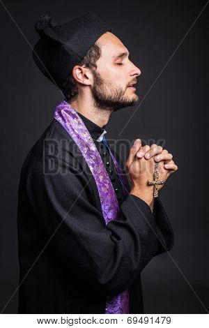 Young priest praying