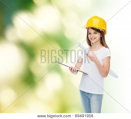 childhood, construction, architecture, building and people concept - smiling little girl in protective helmet with clipboard and blueprint