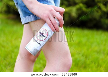Woman spraying insect repellent on skin, outdoor