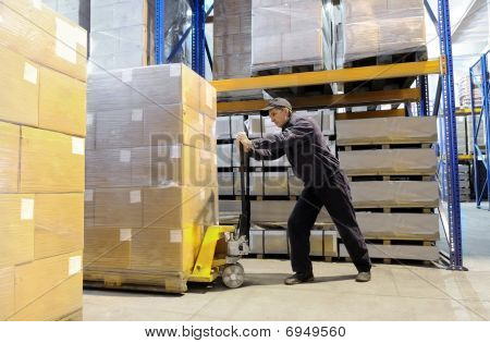 Worker At Warehouse With Loader