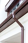 picture of gutter  - New rain gutter with drainpipe on a white plaster wall - JPG
