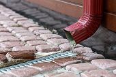 stock photo of red siding  - Rain water runs out of a downspout from the gutter - JPG