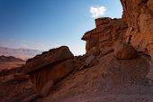Scenic weathered orange rock in stone desert on sunset poster