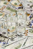 image of two dollar bill  - Two glasses filled with vodka are on dollar bills - JPG