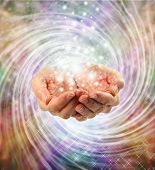 stock photo of quantum  - Female cupped hands emerging from twirling energy field with multicolored background and sparkles  - JPG