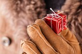 image of courtesy  - a young man wearing a sheepskin coat and holding a very small christmas gift - JPG