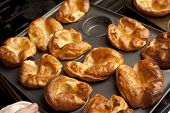 stock photo of trays  - Traditional English Yorkshire puddings made from batter in a baking tray waiting to accompany a meal of roast beef