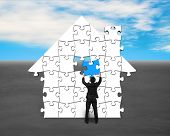 stock photo of last day work  - Finishing house shape puzzles assembling with blue last one - JPG