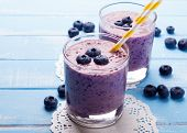 picture of smoothies  - Two glasses of blueberry smoothie on blue colored wooden table - JPG