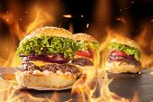 stock photo of hamburger  - Delicious hamburgers with burning flames on background - JPG