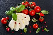 stock photo of black-cherry  - Top view of mozzarella cheese with cherry tomatoes and basil on a black slate surface - JPG