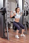 picture of squatting  - Young athletic woman doing squats with the barbell at the gym - JPG