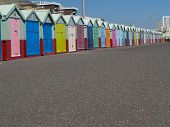 stock photo of beach hut  - Esplanade in front of row or brightly coloured traditional beach huts - JPG