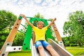 stock photo of chute  - Excited boy with hands up on children chute on playground in summer - JPG