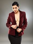 stock photo of braless  - Sexy braless hispanic businesswoman with only her jacket partly letting beautiful breasts to be seen - JPG