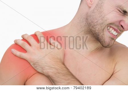 Closeup of young shirtless man with shoulder pain over white background