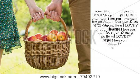 Basket of apples being carried by a young couple against valentines day pattern
