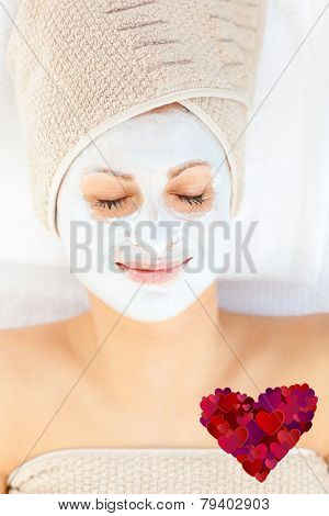 Cute young woman with closed eyes having white cream on her face against heart