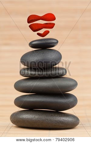 Heart against round smooth pebbles stack close up