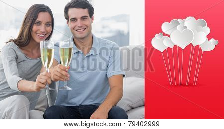 Portrait of lovers toasting their flutes of champagne against hearts