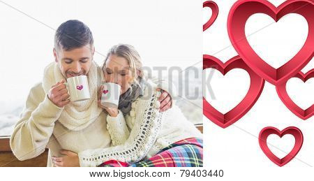Loving couple in winter wear drinking coffee against window against pink hearts