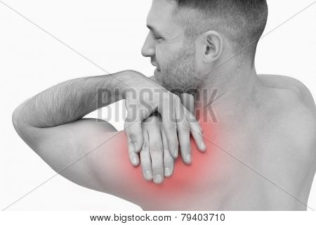 Rear view of shirtless man with shoulder pain over white background