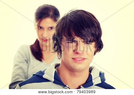 Young beaten up caucasian man standing in front of angry young woman. Couple fight.