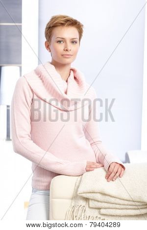 Attractive young blonde woman standing at home behind chair, wearing pink pullover.