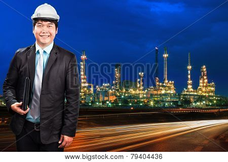Engineering Man And Oil Refinery Plant Against Beautiful Blue Dusky Sky And Vehicle Lighting On Asph