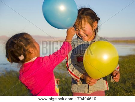 Two little girls playing with each other with balloons.