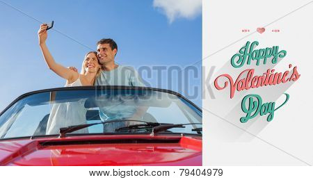 Cheerful couple standing in red cabriolet taking picture against valentines day greeting