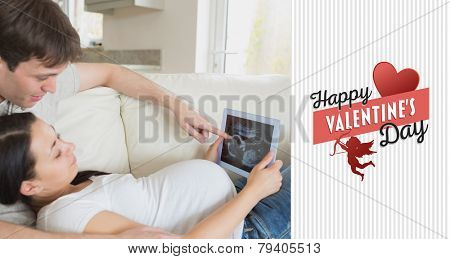 Prospective parents looking at ultrasound scan on tablet pc against happy valentines day