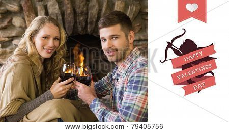 Romantic couple toasting wineglasses in front of lit fireplace against happy valentines day