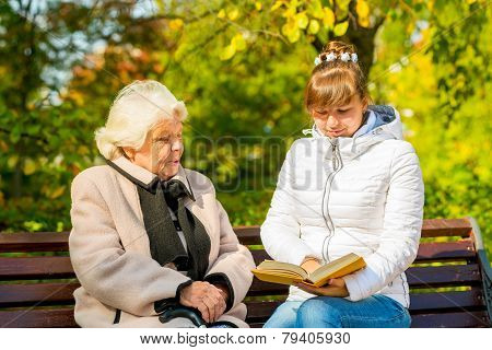 Young Granddaughter Reads His Elderly Grandmother Book