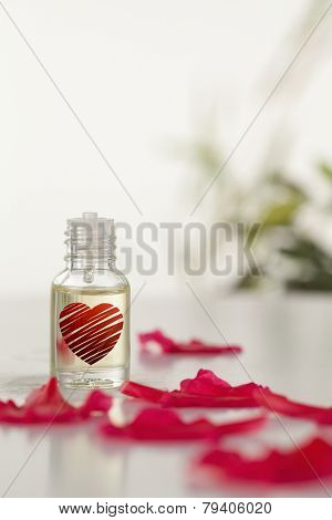 red heart against glass phial and pink petals