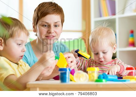 children and woman with colorful plasticine