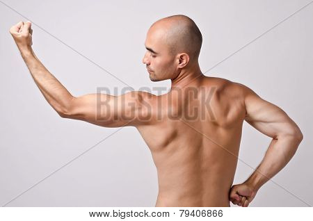 Fit bodybuilder from profile posing with his back.