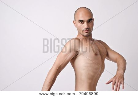 Topless man posing weird, enhancing his chest.