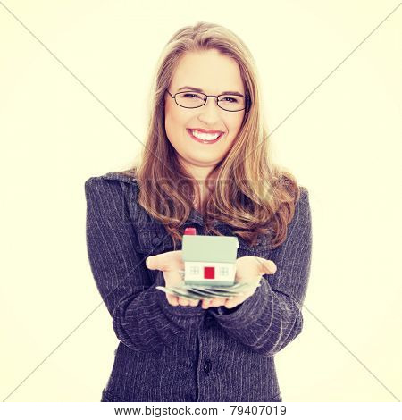Beautiful young businesswoman holding euros bills and house model ,real estate loan concept