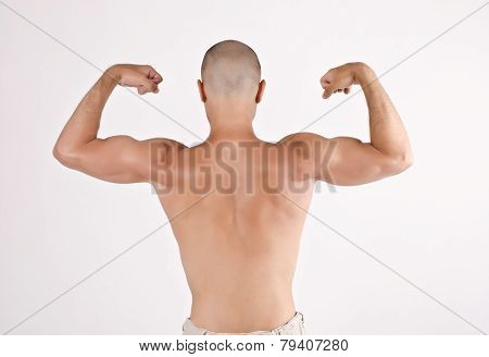 Back of a topless fit man posing with his arms up flexing his biceps and showing his back.