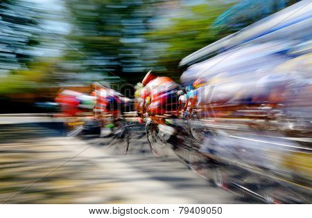 Panning shot of professional cyclists going around the final corner.