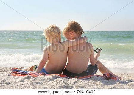 Young Brothers Sitting On Beach By Ocean With Arms Around Each Other